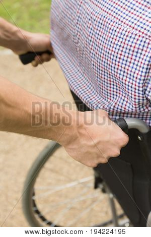 Close up of a man pushing a disabled person on wheelchair