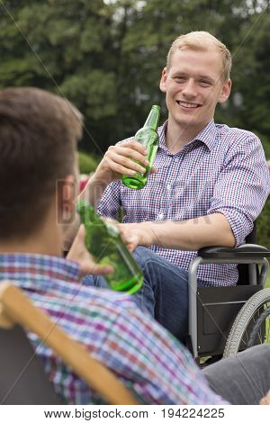 Positive man on wheelchair drinking beer with his friend
