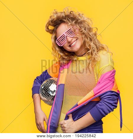 Blonde curly haired girl in shutter glasses wearing colorful jacket and sheer t-shirt holding disco ball.