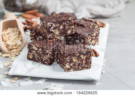 Paleo chocolate energy bars with rolled oats pecan nuts dates chia seeds and coconut flakes horizontal copy space