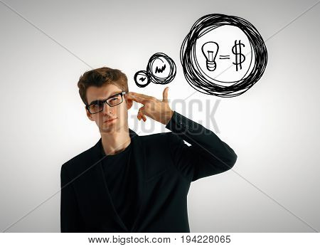 Handsome young businessman with hand put to head as a gun and thought bubble with lamp and dollar equation drawn on gray wall background. Financial ideas concept