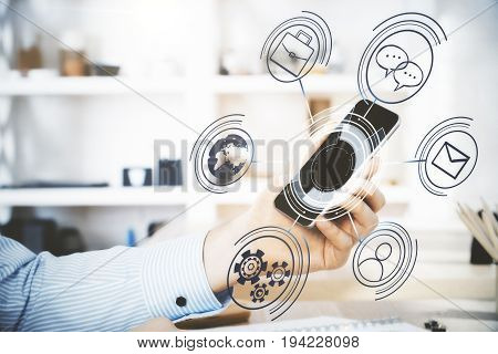 Side view of male hand holding smartphone with abstract digital projection above desktop in modern office. Hologram concept