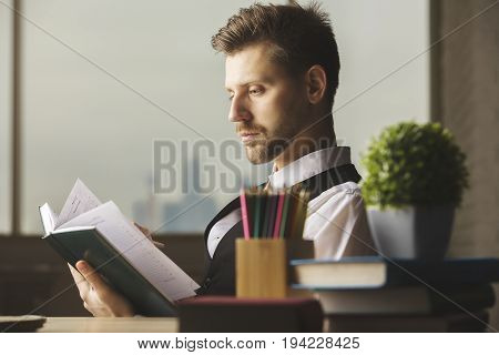 Portrait of handsome young businessman reading book at modern office workplace. Literature concept