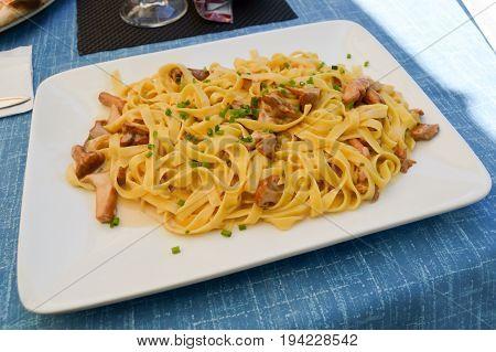 Tagliatelle with porcini mushrooms and cream on a white rectangular dish
