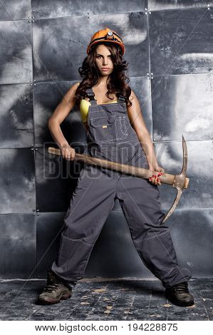 Beautiful sexy worker with a pickaxe. Seductive and beautiful woman miner on a steel background.