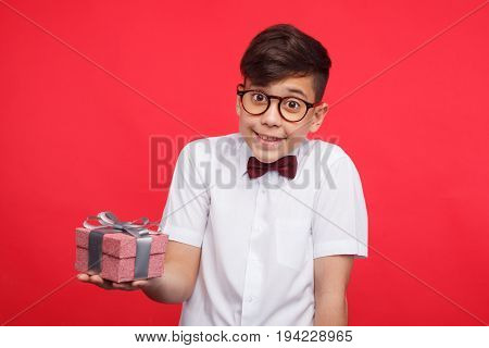Adorable kid in glasses standing with small giftbox on red background and looking at camera.