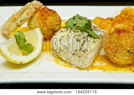 Rectangular plate of baked fish with onion rings and crumbed potatoes