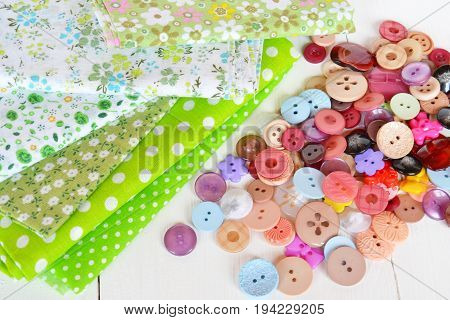 Pieces of cloth with a pattern, different buttons, green bucket