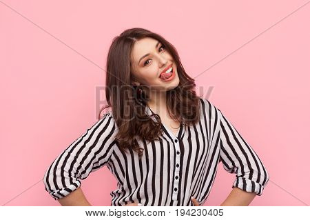 Young charming brunette in striped shirt showing tongue and smiling at camera on pink background.