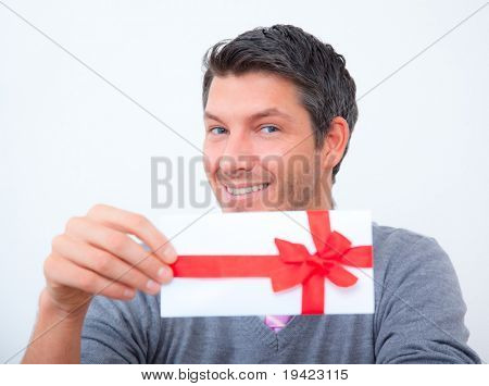 Smiling businessman holding bonuscard with ribbon