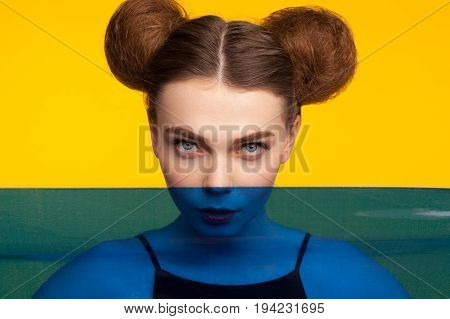 Redhead girl with hair buns staring at camera. Lower part of image is darkened.