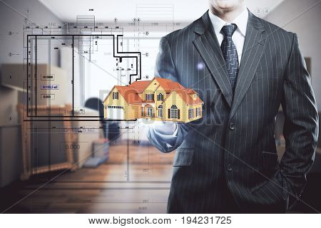 Businessman holding abstract house model in blurry interior with drawings. Housing concept. 3D Rendering