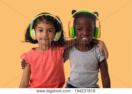 Music and technology concept.Two lovely happy little girls with headphones on yellow background