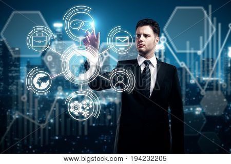 Handsome young businessman pointing at abstract digital business hologram on illuminated night city background. Innovation technology and finance concept. Double exposure