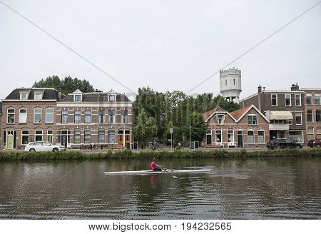 delft netherlands 30 june 2017: delftse schie and woman in canoe in dutch town of delft