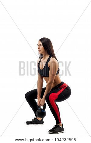 Exercise of squat with weight. A young woman in sportswear makes a squat with a weight in a semi-squat position side view on a white isolated background