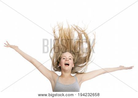 young teen girl with blond wavy hair up in the air against white studio background