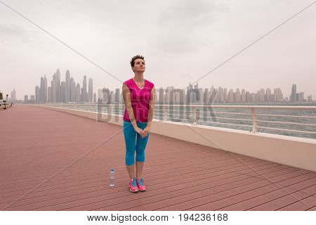 very active young beautiful woman stretching and warming up on the promenade along the ocean side with a big modern city in the background to keep up her fitness levels as much as possible