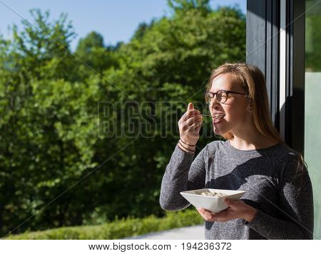 young beautiful successful woman eating breakfast in the doorway of her luxury home villa