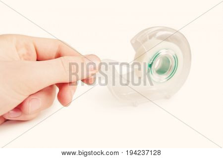 Close-up of man removing adhesive tape from dispenser