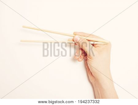 Man's hand gripping chopsticks over white background