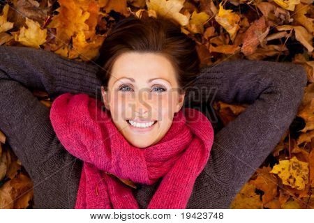 Portrait of relaxing woman on tree enjoying golden autumn fall season