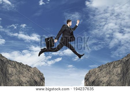 Side view of young businessman jumping over gap on sky background. Faith concept
