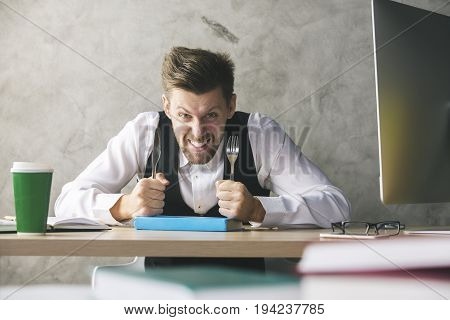 Crazy businessman about to eat blue book with a knife and fork while sitting at wooden office desk with coffee cup and other items