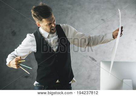 Crazy beast businessman about to tear paper sheet with pencils held as claws