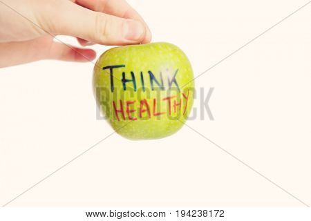 Cropped image of hand holding healthy granny smith apple over white background