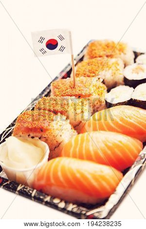 Sushi food on tray with Korean flag against white background