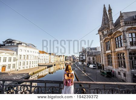 Woman enjoying great view on the water channel standing back on the bridge in Gent city in Belgium