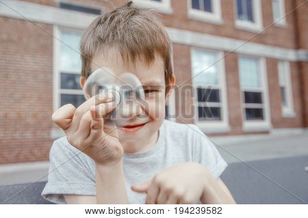 boy turns the fidget spinner and makes faces. child toying with the spinner in the schoolyard