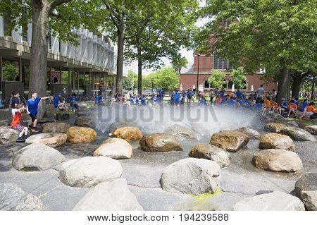 CAMBRIDGE MA, USA - JULY 1 2017: Fountain at Harvard University. People sit around the fountain in Harvard