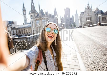 Young woman tourist making selfie photo standing on the bridge with beautiful view on Gent city in Belgium