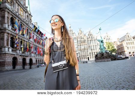 Portrait of a young woman tourist walking with photo camera on the Great Market square in Antwerpen city in Belgium