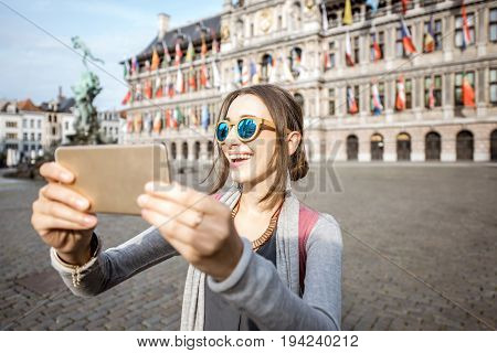 Young woman tourist making selfie photo with city hall on the background standing on the Great Market square in Antwerpen, Belgium