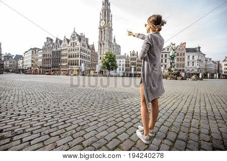 Young woman tourist showing with hand famous cathedral tower standing on the Great Market square during the morning in Antwerpen, Belgium