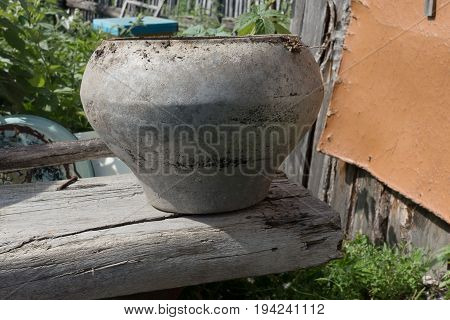 Old Cast-iron cauldron on a wooden board.