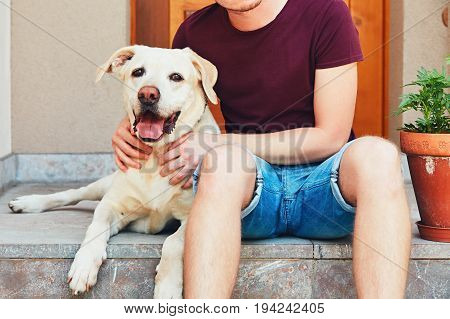 Happy labrador retriever. Young man resting with old dog on the stairs in front of the house.
