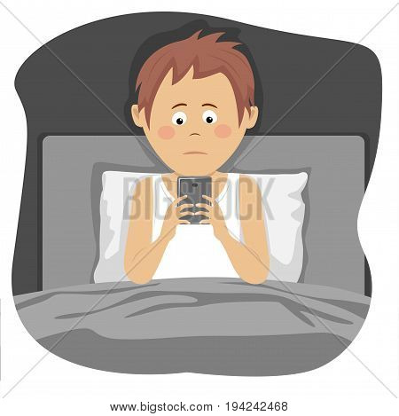 Teenager boy uses a smartphone sitting in bed at night