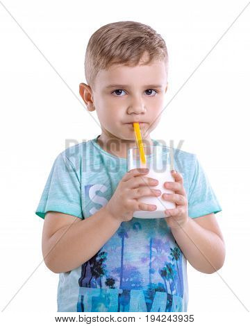 Pretty little boy is drinking a glass full of milk from yellow straw isolated on a white  blackground. A cute little child holds a glass of milk on gray background. Healthy and dairy products.