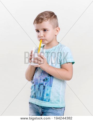 Charming little boy in a blue t-shirt drinks milk from a yellow straw. A cute little boy is holding a glass of milk. Adorable little boy is drinking fresh milk on gray background.