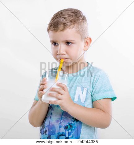 Adorable little boy holding a glass of organic milk and drinking fresh milk on gray background. Close-up portrait of a cute little kid in a blue T-shirt with a full glass of milk from yellow straw.
