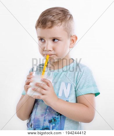 Cute little boy holding a glass of milk and drinking fresh milk. A little kid standing in blue shirt and drinking milk in a glass from a yellow straw. A nice little kid with milk. Healthcare.
