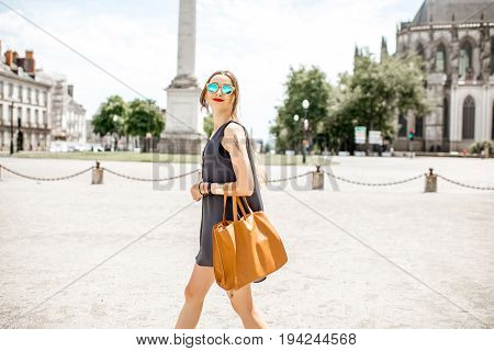 Young woman walking on the square with Louis column and saint Pierre cathedral on the background in Nantes city in France