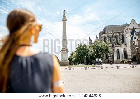 Young woman enjoying view on the Louis column and saint Pierre cathedral in Nantes city in France