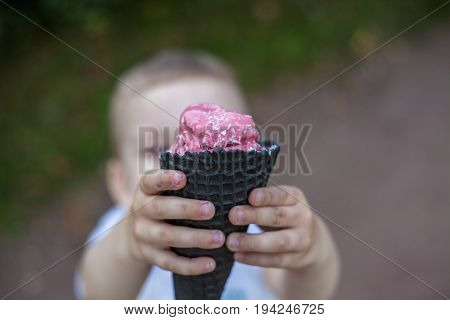 A child is holding a pink ice cream