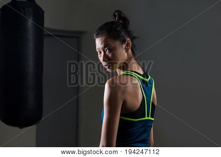 Portrait of determined woman standing in fitness studio