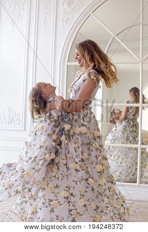 mother and daughter dancing in the mirror in the same dress in a big white room